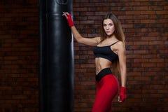 Молодые женщины кладя в коробку, сумка бокса красная повязка на руках Стоковые Фотографии RF