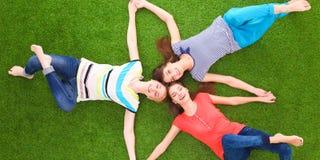 Молодые женщины лежа на зеленой траве Стоковое фото RF