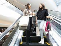 Молодые женщины наслаждаются ходить по магазинам совместно в выходных Стоковое Фото