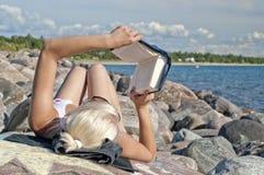 Молодые женщины на пляже читая книгу Стоковое Фото