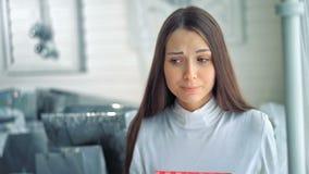 Молодые женщины несчастны о ее подарке рождества и смотреть унылы сток-видео