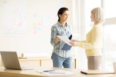 Молодые женщины обсуждая работу в офисе Стоковые Изображения RF