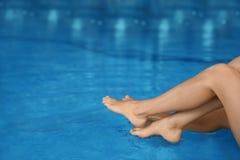 Молодые женщины ослабляя в голубом бассейне, крупном плане Стоковая Фотография RF