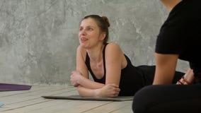 Молодые женщины отдыхая на работать циновку и разговаривать с друзьями перед разминкой спорта Стоковое Изображение