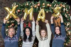 Молодые женщины показывая xmas слова сделанный из золотых воздушных шаров Стоковые Изображения