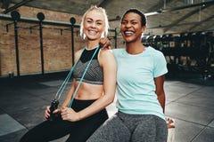 Молодые женщины пригонки смеясь после встречи разминки спортзала совместно стоковое изображение rf