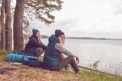Молодые женщины путешественника отдыхая во время путешествовать около озера Стоковое Фото