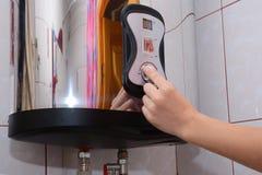Молодые женщины рук установили температуру воды в электрическом котле Закройте вверх женских рук поворачивая ручку Стоковое фото RF