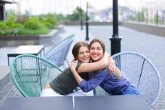 Молодые женщины сидя на кафе снаружи Стоковые Изображения RF