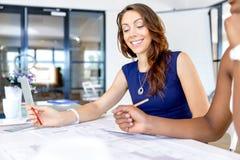 Молодые женщины сидя на столе в офисе и работая на светокопии Стоковое Изображение RF