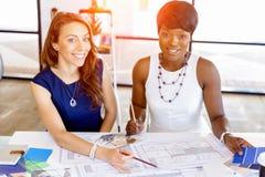 Молодые женщины сидя на столе в офисе и работая на светокопии Стоковое Изображение