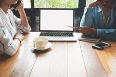 Молодые женщины сотрудников сыгранности дела работая в кафе с компьтер-книжкой, Стоковая Фотография RF