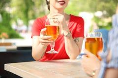 Молодые женщины с стеклами пива на таблице Стоковые Изображения RF