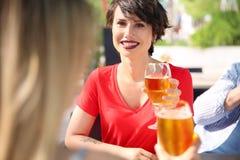 Молодые женщины с стеклами холодного пива на таблице Стоковая Фотография RF