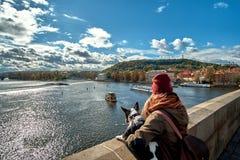 Молодые женщины туристские при собака щенка и рюкзак смотря туристскую шлюпку и лебедей плавая на реке Влтавы стоковая фотография rf