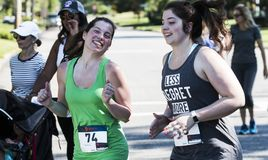 Молодые женщины усмехаются на камере на гонке дороги 5K стоковое изображение