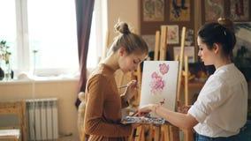 Молодые женщины учитель рисования и студент имеют урок в крася школе, девушке смешивают цвета на мастере промежутка времени палит сток-видео