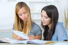 Молодые женщины читая и studing совместно Стоковые Фотографии RF