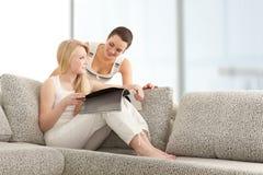 Молодые женщины читая кассету книга на софе Стоковые Изображения RF