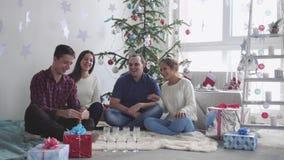 Молодые жизнерадостные друзья празднуя рождество сидят перед рождественской елкой имея потеху Концепция праздновать новая акции видеоматериалы