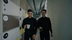 Молодые жизнерадостные коллеги говоря, идущ вдоль коридора, выпивая кофе внутри помещения видеоматериал