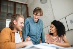 Молодые жизнерадостные люди обсуждая что-то в офисе 2 мальчика с светлыми волосами и девушкой с темной деятельностью вьющиеся вол Стоковые Фотографии RF