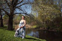 Молодые идти, ход беременной женщины путешественника, поворачивающ вокруг и наслаждаются ее свободным временем отдыха в парке с стоковые фото
