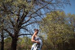 Молодые идти, ход беременной женщины путешественника, поворачивающ вокруг и наслаждаются ее свободным временем отдыха в парке с стоковая фотография