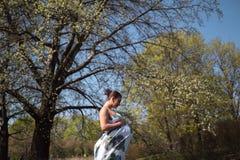 Молодые идти, ход беременной женщины путешественника, поворачивающ вокруг и наслаждаются ее свободным временем отдыха в парке с стоковая фотография rf
