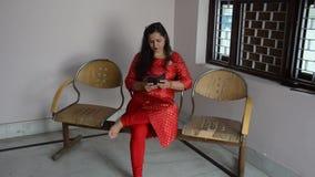 Молодые индийские женщины используя смартфон видеоматериал