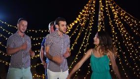 Молодые и напористые друзья танцуют и поют снаружи на диско на ноче видеоматериал