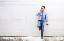 Молодые и современные привлекательные стойка и беседа бизнесмена через умное Стоковые Изображения