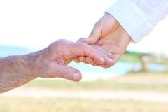 Молодые и старшие женщины держа руки Стоковое Фото