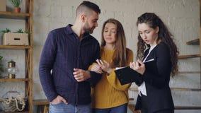 Молодые клиенты смотрят документы и обсуждают условия дела с маклером по операциям с недвижимостью пока стоящ внутренность новая акции видеоматериалы