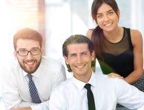 Молодые коллеги дела на заднем плане офиса Стоковое фото RF