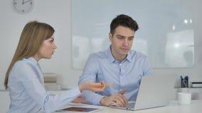 Молодые коллеги дела обсуждая проект на ноутбуке, противоречат
