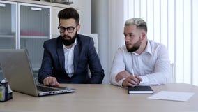 Молодые коллеги дела работая на новом проекте на компьтер-книжке сток-видео