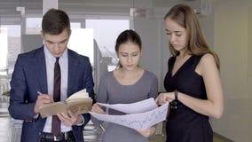 Молодые коллеги обсуждают документы стоя в современном офисе сток-видео