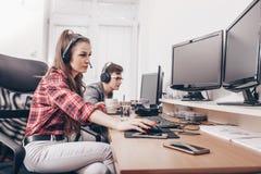 Молодые коллеги работая в офисе с шлемофоном стоковые изображения rf