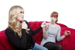 Молодые красивейшие белокурые и красные с волосами девушки получают сигарету отсутствующей дальше стоковое фото rf