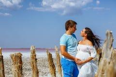 Молодые красивые женатые пары, беременная женщина в белом платье в природе, счастливых родителях ждать младенца стоковые фото