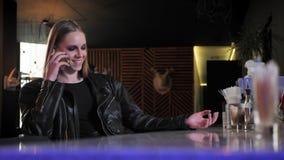 Молодые красивые женщины в черной куртке с тяжелой составляют сидеть и говорить на телефоне, смеясь над, предпосылке бара сток-видео