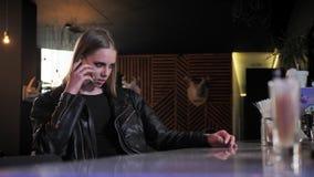 Молодые красивые женщины в черной куртке с тяжелой составляют сидеть и говорить на телефоне, сердитом, предпосылке бара видеоматериал