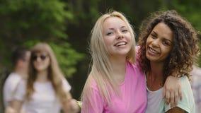 Молодые красивые женщины обнимать, усмехаясь на камере, группа в составе молодые люди partying акции видеоматериалы