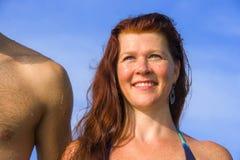Молодые красивые и счастливые пары на женщине волос withl пляжа красной  стоковое фото