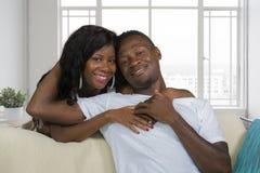Молодые красивые и счастливые черные Афро-американские пары в любов ослабленной на современной домашней помадке живущей комнаты п стоковая фотография