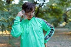 Молодые красивые кавказские беседы человека на мобильном телефоне стоя в парке стоковое изображение