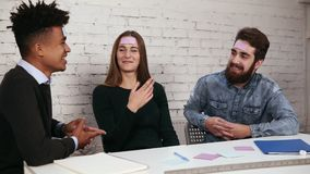 Молодые красивые люди в офисе сидя на таблице играя игру имени с примечаниями стикера sticked к их лбу сток-видео