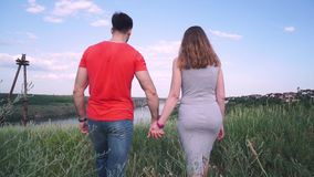 Молодые, красивые парень и девушка держат руки и идут вперед, на фоне моста, река, дерево, небо акции видеоматериалы