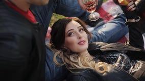 Молодые красивые пары в кожаных куртках на пикнике выпивая красное вино в стеклах сток-видео